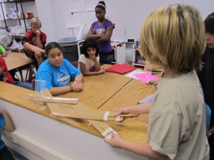 "6th graders test their ""robotic"" arm's strength."